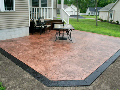 Stamped and stained back yard patio with black stained concrete edge and rustic red concrete inside.