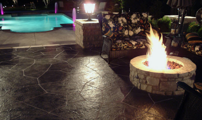 Stamped concrete fire pit along side of a concrete pool deck and a lighted outdoor light.