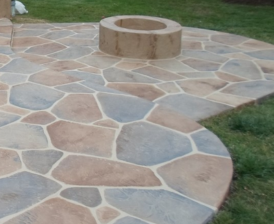 One of a kind stamped patio with a concrete fire place in the middle in Kalamazoo, Michigan.