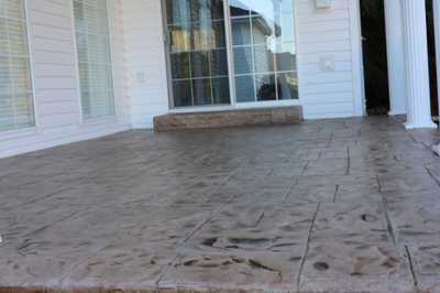 Stamped concrete patio outside of Kalamazoo, Michigan with a sliding door and concrete step.