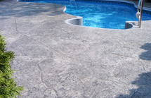 Pool deck in Portage, Michigan with a stamped concrete design.