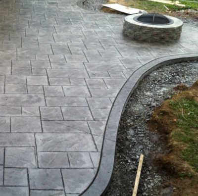 Gray stamped patio with built in concrete brick fire pit.